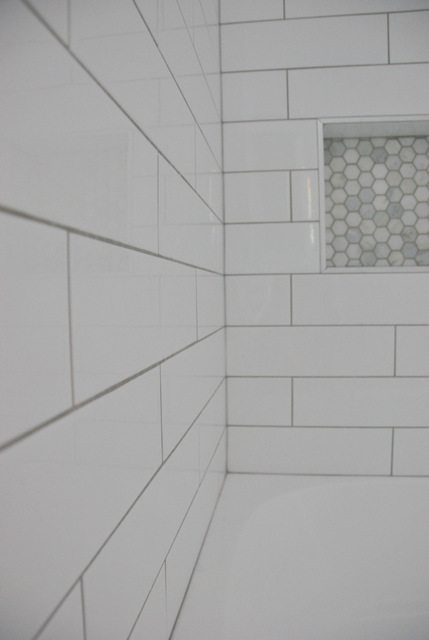 shower design with subway tile and marble tile niche