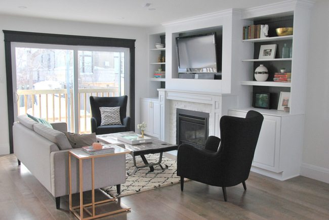 living room featuring black wingback chairs (the polo by structube) with fireplace built ins and grey couch - via the sweetest digs