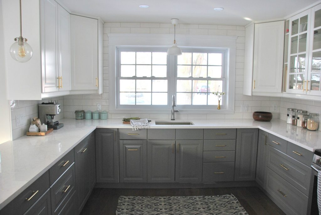 installing gold cabinetry hardware in a grey and white kitchen - via the sweetest digs