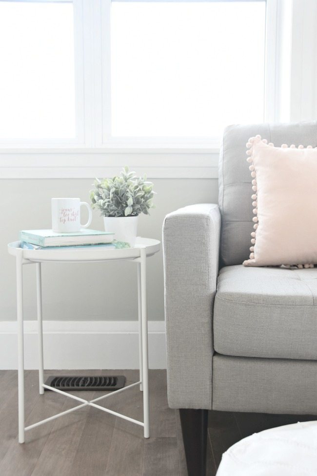 Create a master bedroom reading corner with a cozy chair, side table, white leather pouf, and throw pillows. Click for sources and tips on designing your reading nook.