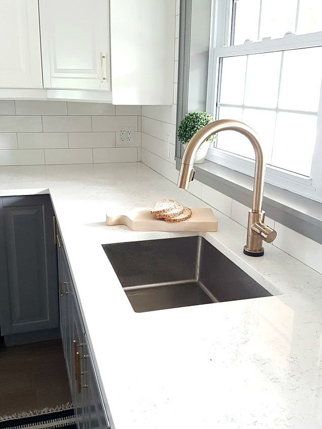 Can you mix metals in a kitchen? Here is how we mixed a stainless steel sink with a brushed gold kitchen faucet by Delta (the Trinsic). Result: Gorgeous! See the rest of our gray and white kitchen, and get all of the design sources, in the post!
