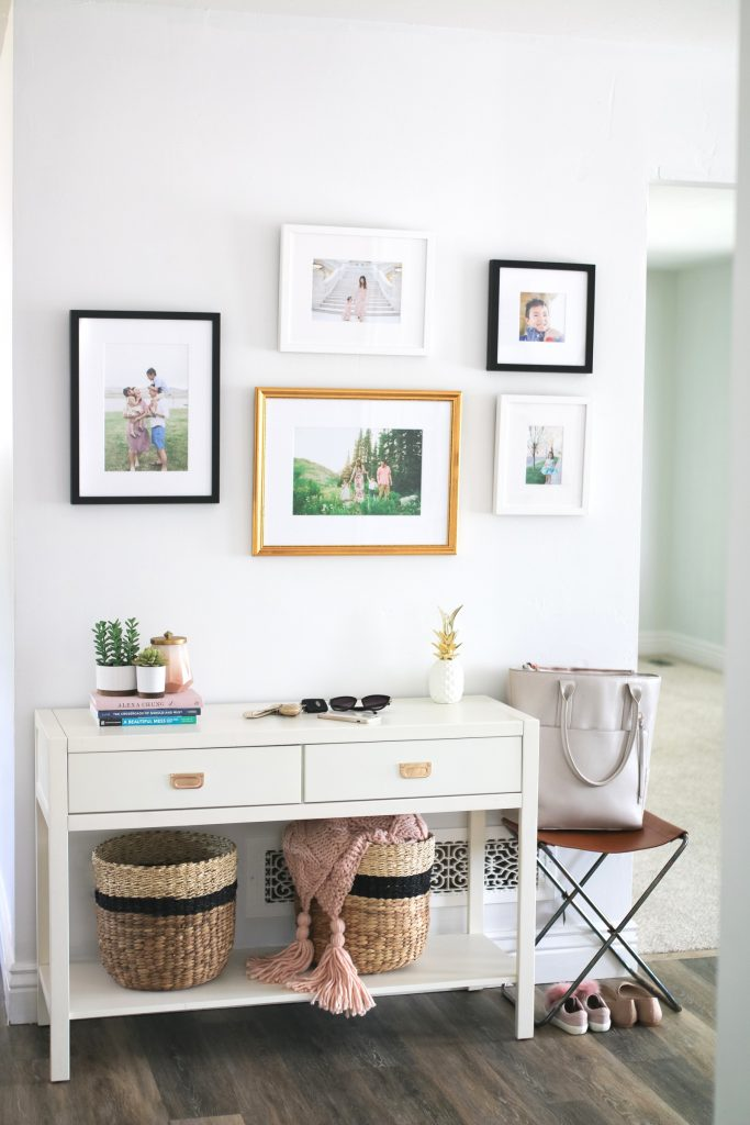A white, modern entryway featuring a gallery wall, baskets, and console table by Sandy.