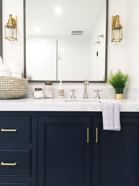 Dark blue bathroom vanity with mixed metals - chrome and brass. So pretty! Via Sarah from Making Joy and Pretty Things.