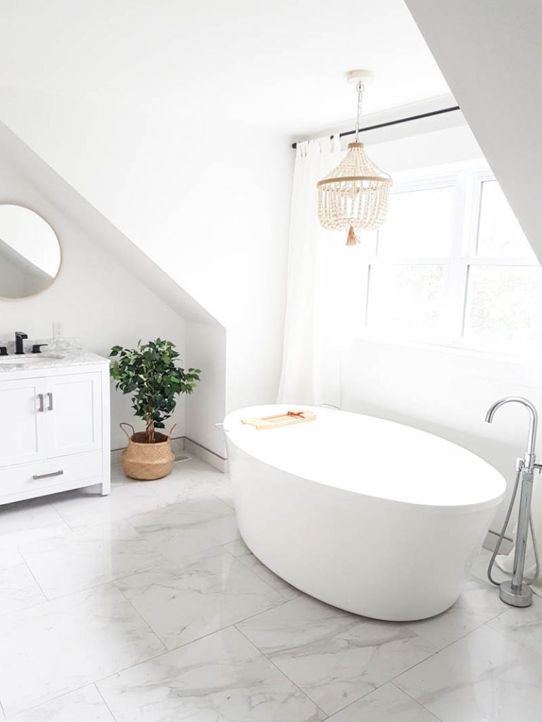 Master #Bathroom Makeover featuring white walls, marble tiles, wood bead chandelier, freestanding tub, and more. A really pretty design for a spa-like bathroom!