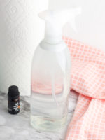 DIY window cleaner in a spray bottle next to paper towels, a red cloth and essential oil.