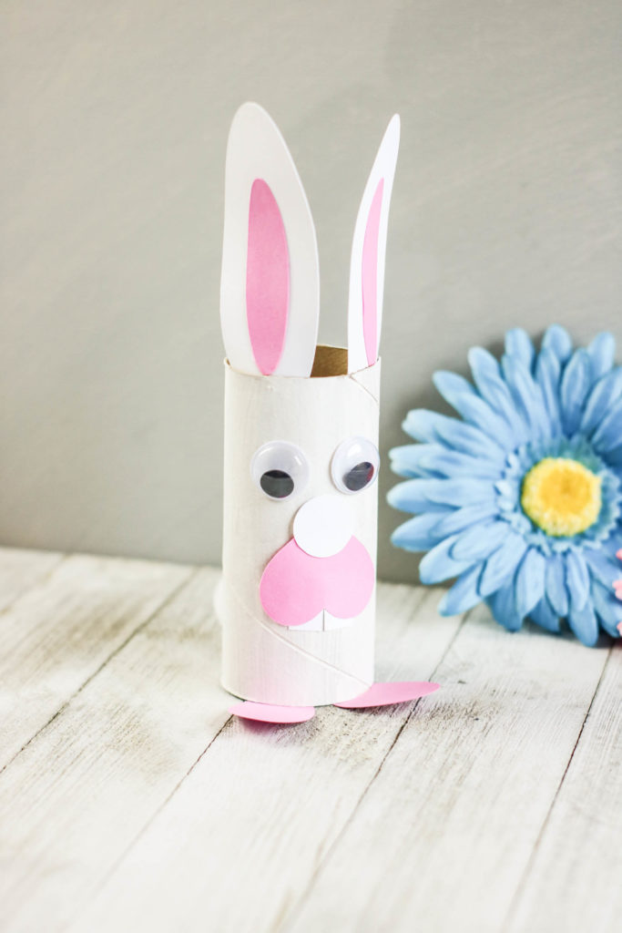 Toilet roll Easter bunny next to a blue flower.