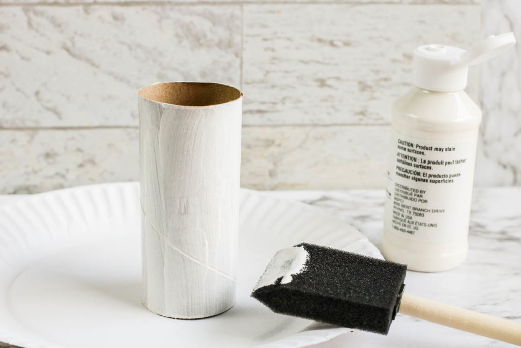Painting a toilet paper roll.