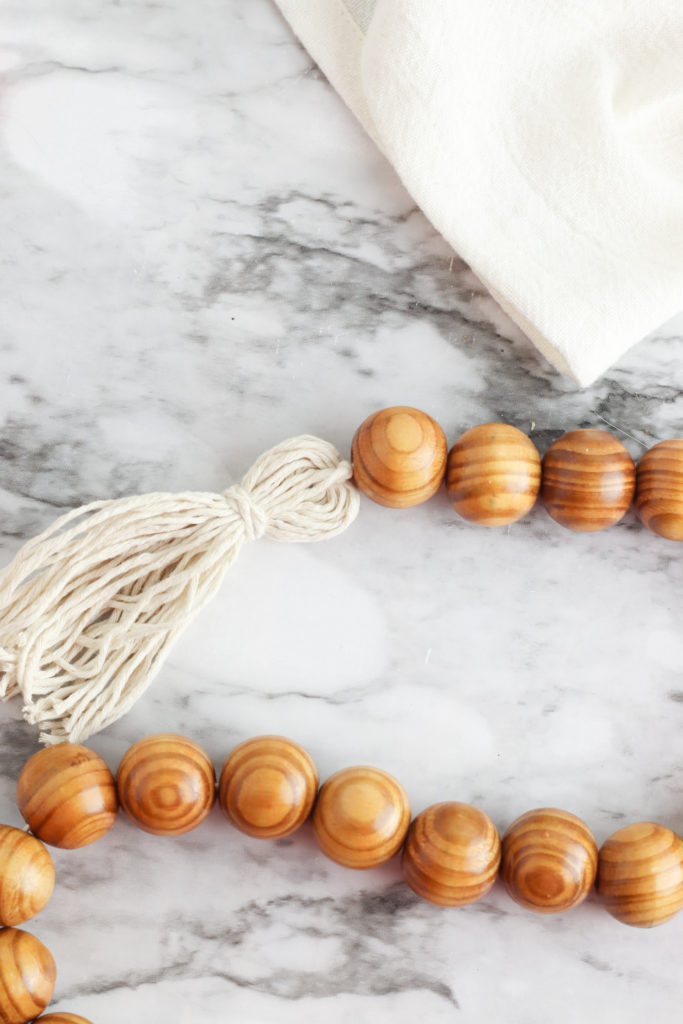 Attaching a tassel to the end of the wood bead garland