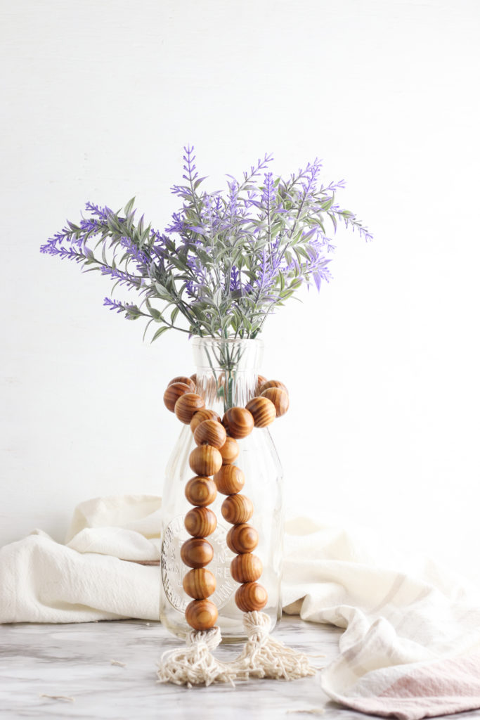 Wood bead tassel garland wrapped around a vase with purple flowers.