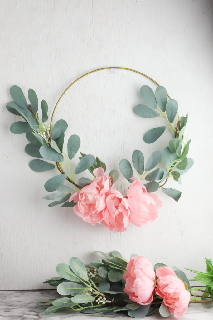 Floral hoop wreath hung on a wall.