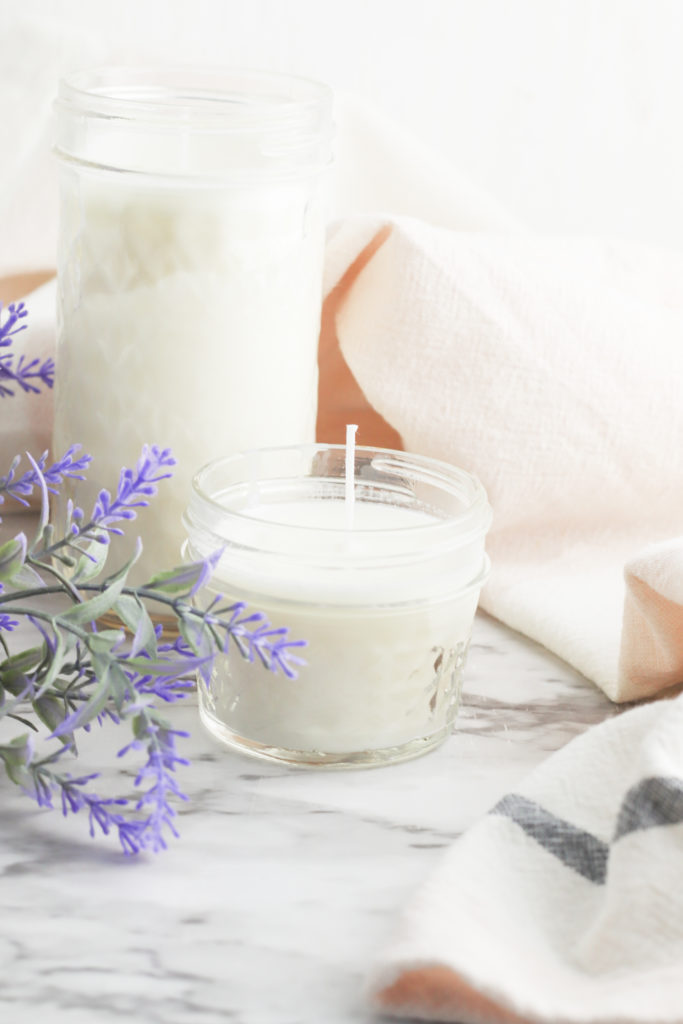 Finished soy candles next to lavender flowers.