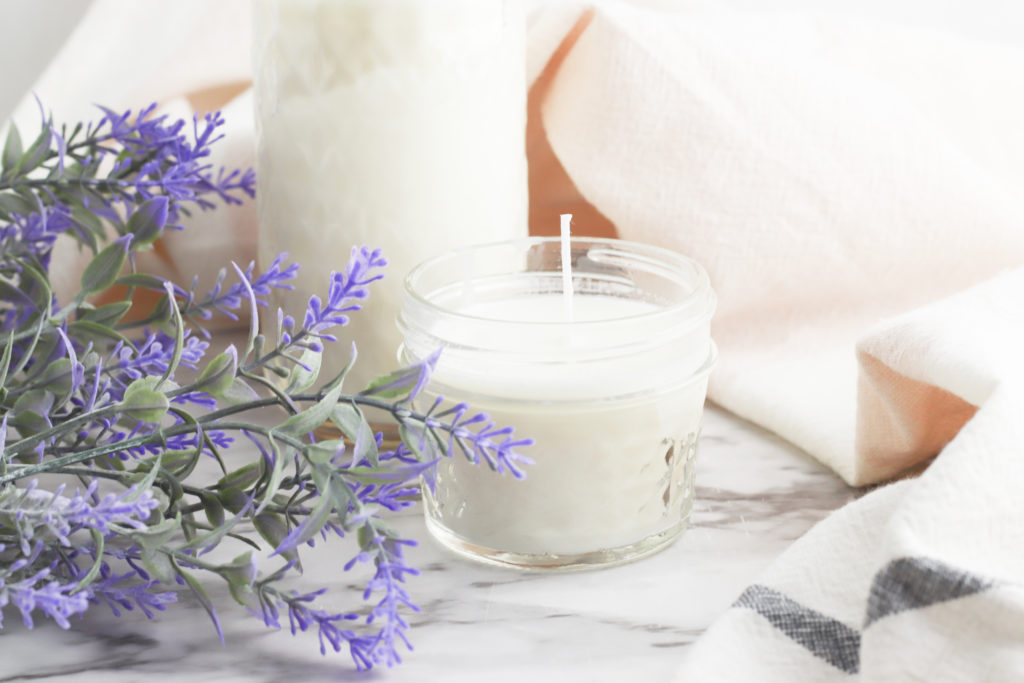 Glass soy candles next to lavender flowers.