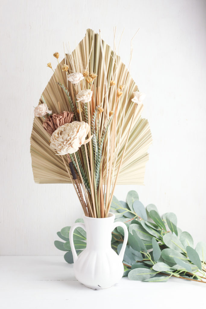 Dried palm leaf flower bouquet displayed in a white vase.