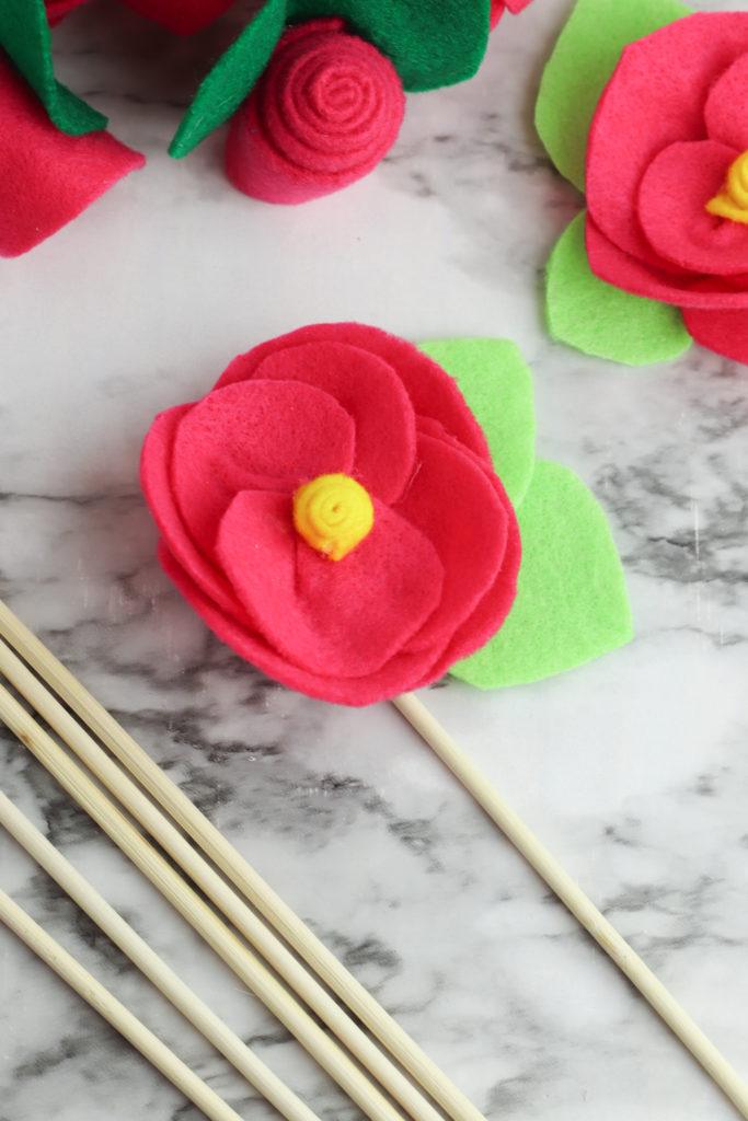 Attaching the felt flower to a dowel rod.