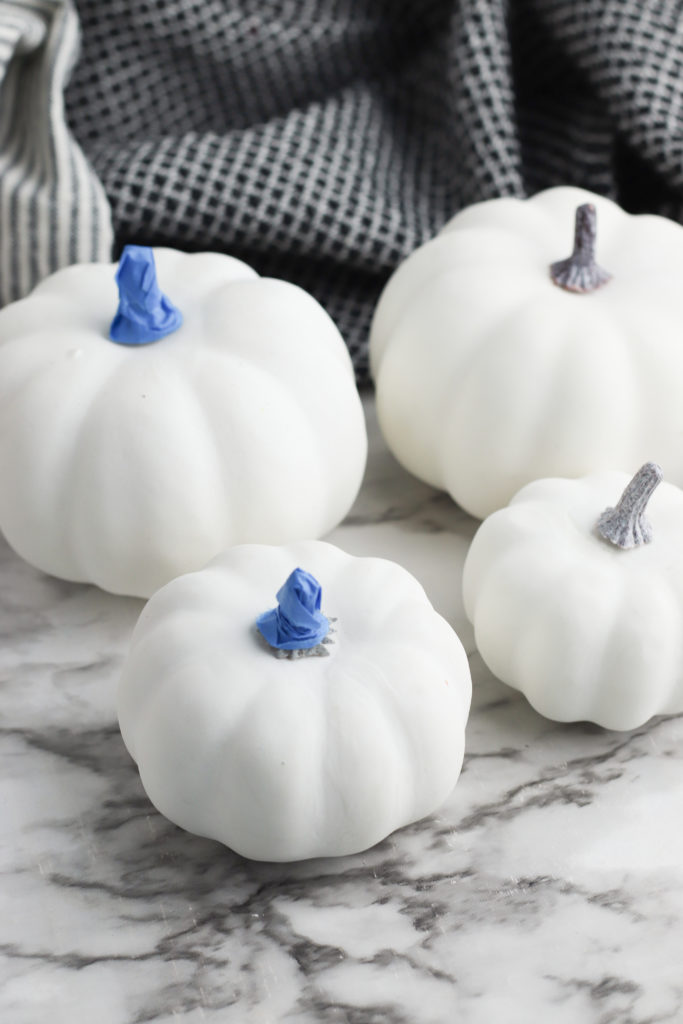 White pumpkins with blue masking tape covering the stem.